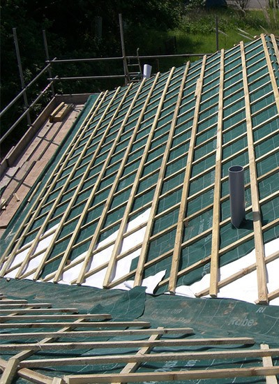 Roofers laying roof tiles